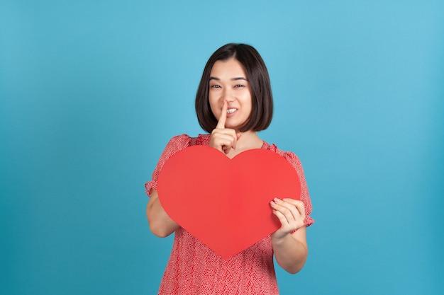 Таинственная азиатка в красном платье держит большое красное бумажное сердце и палец у рта