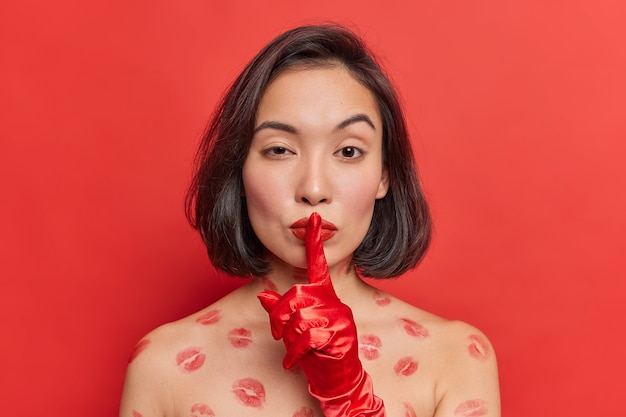 검은 머리를 한 신비한 아시아 여성이 침묵의 제스처를 취하며 셔츠를 입지 않은 채 빨간 립스틱을 바르고 쉿 소리를 자신감 있게 보이게 하는 비밀 정보 포즈를 알려줍니다.