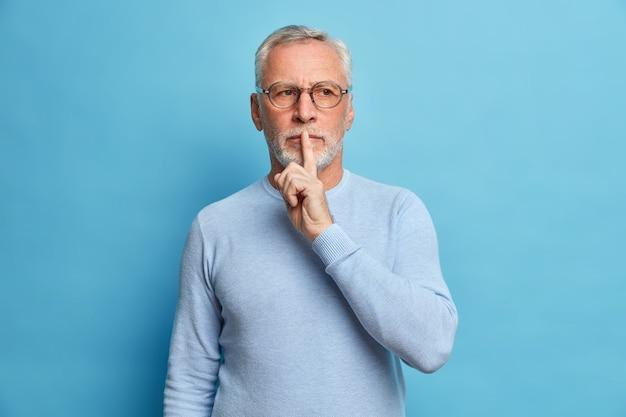 신비한 수염 난 남자가 침묵 제스처를 만든다 사려 깊은 표정이 조용 해지라고 요구합니다 비밀은 파란색 벽 위에 고립 된 캐주얼 점퍼와 광학 안경을 착용합니다.