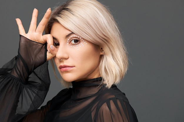 Mysterious beautiful young caucasian female with artistic bright make up and nose ring wearing trendy transparent blouse with enigmatic look, making gesture with fingers at her eye