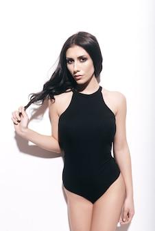 신비한 아름다움. 검은 수영복을 입은 매력적인 젊은 여성이 머리를 만지고 흰색 배경 앞에 서 있는 동안 카메라를 보고 있습니다.