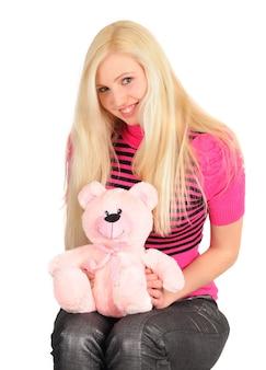 白でポーズをとるピンクのドレスのおもちゃのクマとキャンディーを持つ神秘的なブロンドの女の子