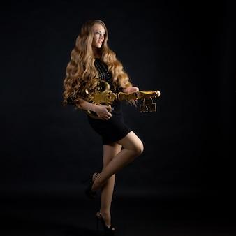 Таинственная блондинка с золотым ключиком, мистическая тайна, концепция. красота портрет привлекательной молодой женщины с роскошными вьющимися волосами, фото на темном фоне