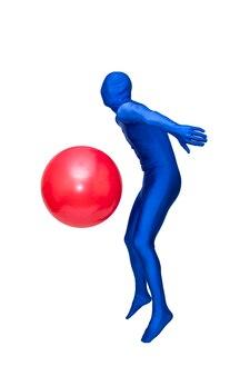 ピラティスボールと青いスーツの運動の神秘的な青の男