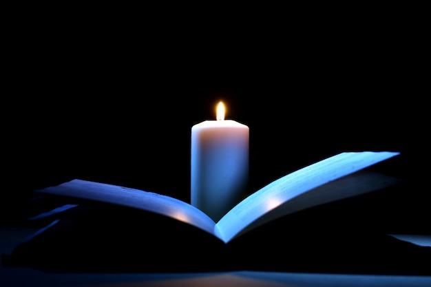 Mysterious book and candle on black.