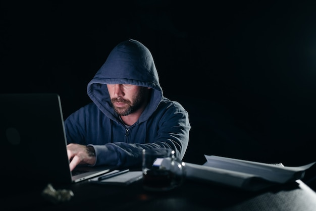 Mysterious criminal man in a hood hacks a laptop in the dark