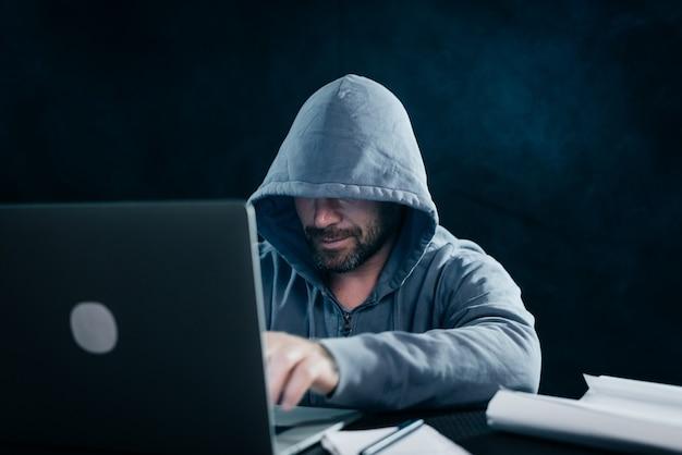謎の狡猾な男がボンネットの下に顔を隠し、暗闇の中でラップトップをハックする