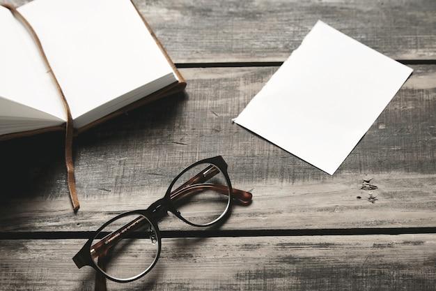 Загадочная детективная игровая концепция. открытый блокнот в кожаном переплете, лист белой бумаги и пара очков из нержавеющей стали, изолированные на черном состаренном деревянном столе. вид сбоку