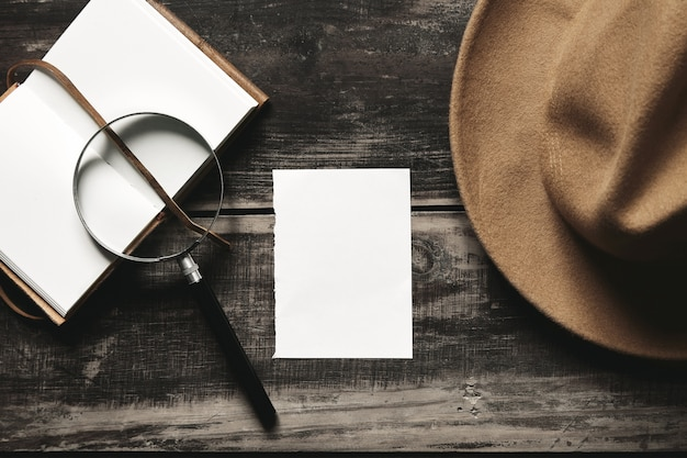 Mysterious detective game concept. opened notebook in leather cover, sheet of white paper, felt brown hat and big vintage magnifier steel glasses isolated on black aged wood table. top view.