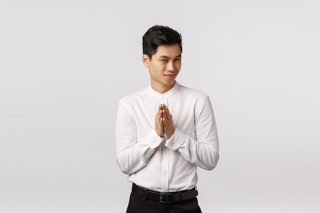 Mysterious and devious young good-looking asian businessman in white shirt, pants, rub hands and squinting sly, have secret evil plan, relish good deal, make money, standing