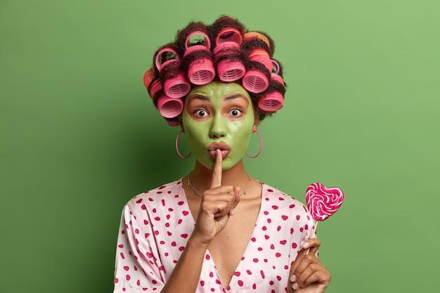 Таинственная этническая женщина носит зеленую маску для лица и бигуди для волос, делает жест молчания, рассказывает секрет, держит восхитительный леденец в форме сердца, делает прическу, носит халат, проводит время дома