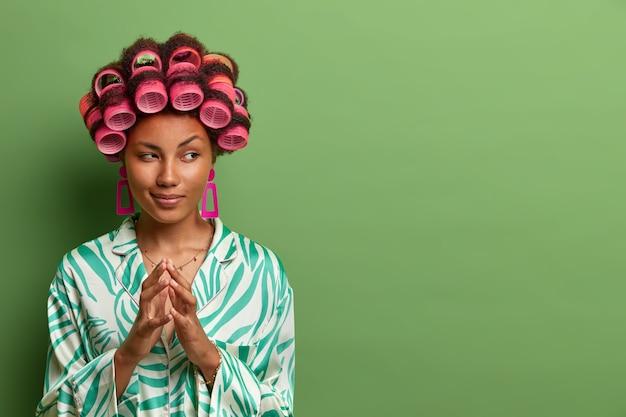 頭にヘアカーラーを持ち、指を尖らせて何かを計画し、目をそらし、アイデア、空想、カジュアルな家庭服を着て、緑の壁に隔離された、神秘的な格好良い女性