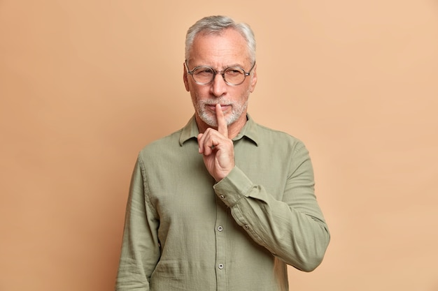 Mysterious grey haired man makes silence gesture and looks with cunning expression has tricky plan presses index finger to lips dressed in formal shirt asks to remain silent