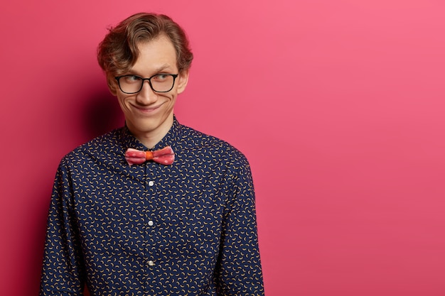 Mysterious happy adult man has broad smile on face, concentrated aside, stands indoor over rosy wall, has nice conversation with coworkers, dressed formally, isolated over pink wall, blank space