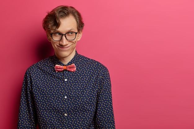 神秘的な幸せな大人の男は、顔に広い笑顔を持って、脇に集中し、バラ色の壁の上に屋内に立って、フォーマルな服を着て、ピンクの壁の上に隔離され、空白のスペースで同僚と素敵な会話をしています