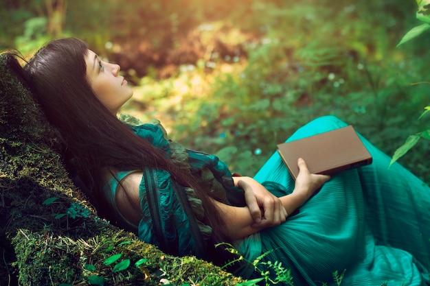 森の中で美しい女性の神秘的なイメージ。野生の自然を背景にした孤独な謎の少女。自分探しをする女性