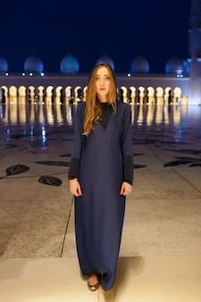 Mysterious lady wearing long dress with hood stands before entrance to shekh zayed grand mosque