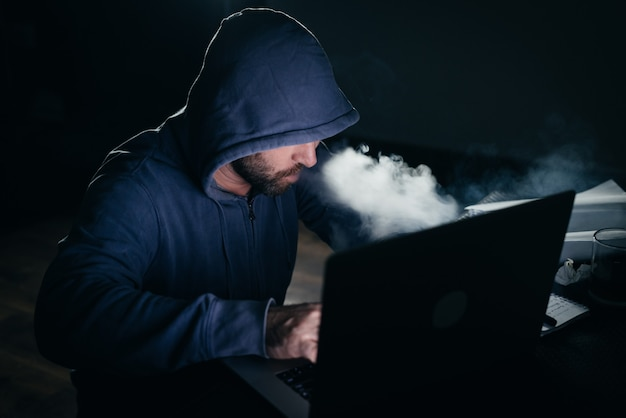 Mysterious man hacker in the hood doing something illegal on the laptop, in the dark, smoking a hookah