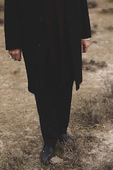 Таинственный мужчина в черном костюме и туфлях