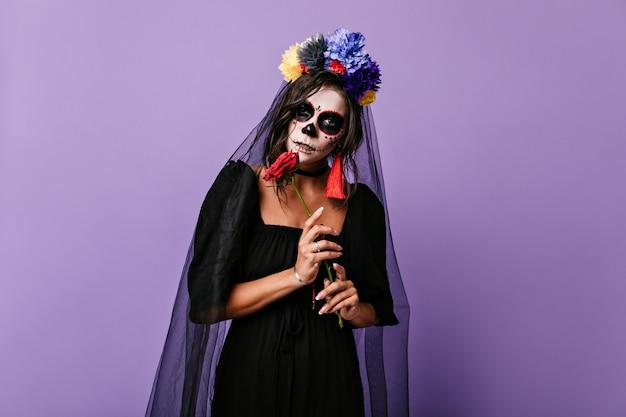 Misteriosa donna messicana in abito di vedova nera in posa sulla parete lilla. foto di ragazza con corona di fiori e orecchini luminosi.