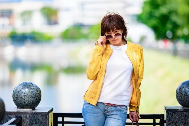 メガネとカジュアルな服を着た謎の中年女性が都会でポーズをとるサングラスを慌てて脱ぐ