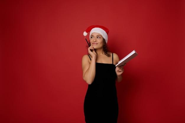 산타 모자를 쓴 신비한 혼혈 미녀는 메모장을 들고 빨간색 배경의 복사 공간에 연필로 사려깊게 가리키고 있습니다. 광고에 대한 크리스마스와 새해 계획 개념.
