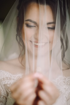 Mysterious portrait of a bride hidden under the veil and holding a wedding ring