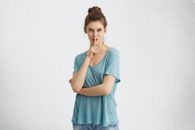 謎めいた唇に人差し指を保持しているルーズブルーのカジュアルなtシャツを着ている髪のお団子を持つ神秘的なきれいな女性。秘密を守り、静かにすることを求める青い魅力的な目を持つ美しい女性