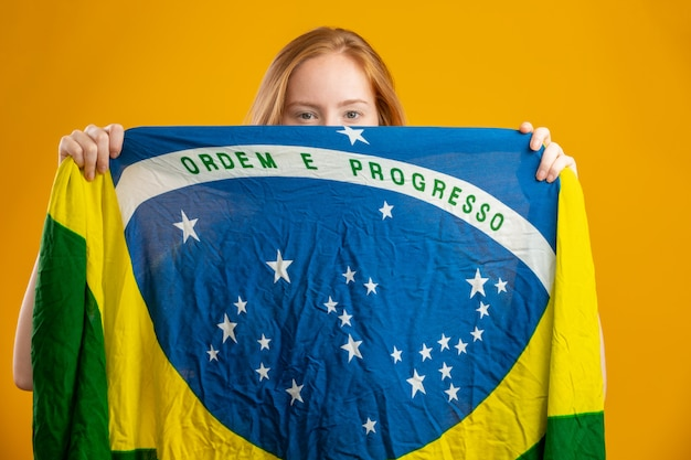 Mysterious redhead woman fan holding a brazilian flag in your face. brazil colors flag, green, blue and yellow. elections, soccer or politics.