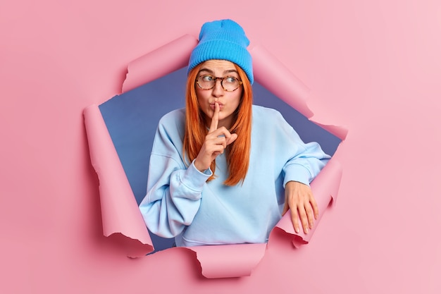 Таинственная рыжая женщина делает жест молчания, просит не рассказывать ее секрет, носит синюю шляпу и свитер, распространяет слухи, смотрит в сторону, пробивает бумажную стену. понятие языка тела. заговор.
