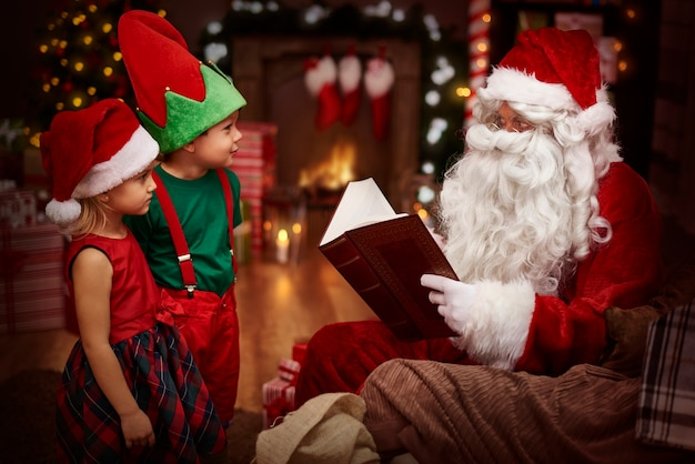 Mysterious santa claus reading a book with children
