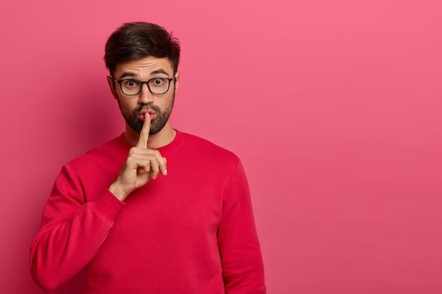 Mysterious surprised bearded man makes hush gesture, tells secret and whispers rumors