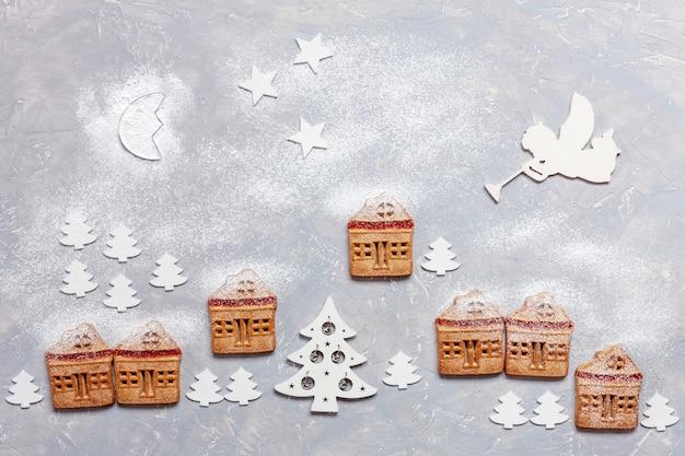木製のクリスマスツリーの装飾が施された自家製のクリスマスクッキーで作られた神秘的な冬の村