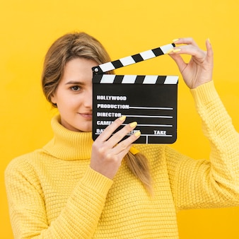 Mysterious woman holding clapboard