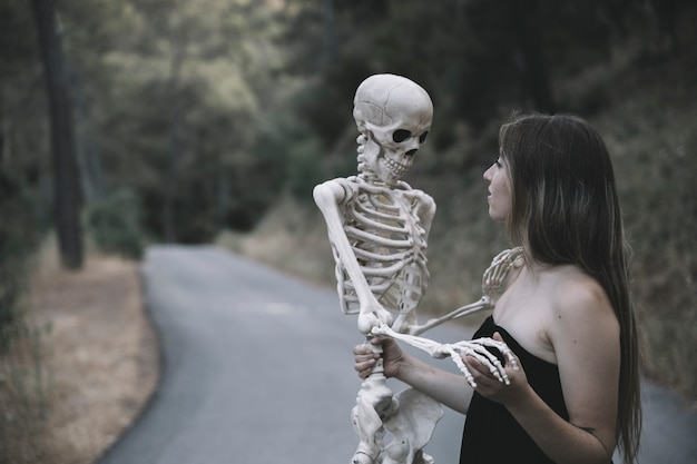 Mysterious woman holding skeleton