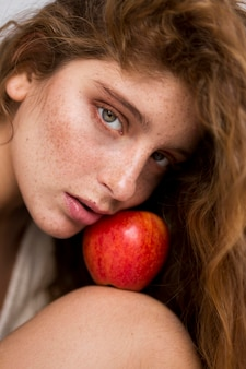 Mysterious woman posing with red apple close-up
