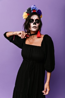 Mysterious woman with image of skeleton on her face is trying to rip black necklace off her neck.
