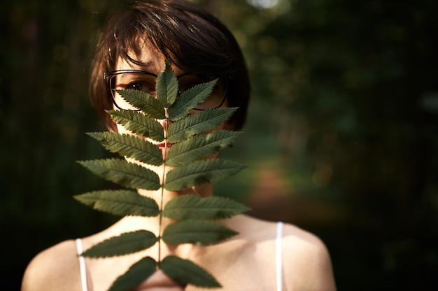Misteriosa giovane donna con capelli corti bruna e occhi scuri in posa nei boschi, che copre il viso con una grande foglia verde, godendo della natura selvaggia