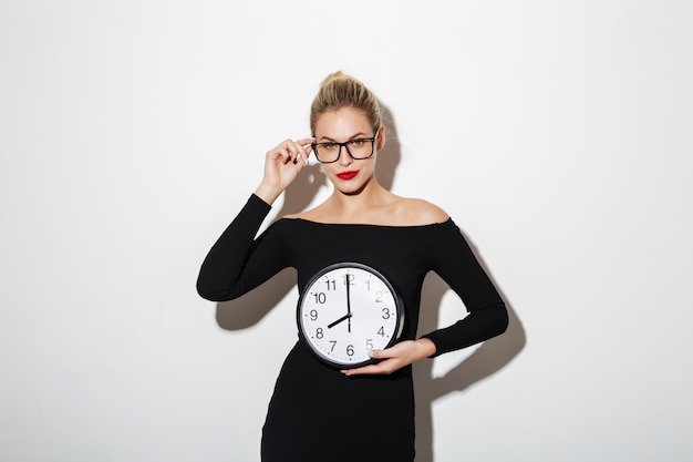 Mystery business woman in dress and eyeglasses holding clock