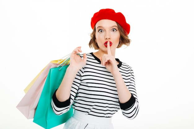 Mystery ginger woman holding packages and showing secret gesture while looking at the camera
