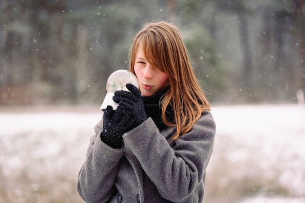 A mystery girl with a surprised face examines a magical crystal glass snow ball. energy emotion
