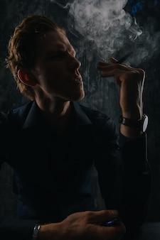 黒の背景に分離された葉巻と煙を持つ謎の男