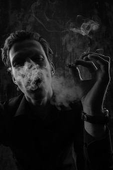 Mystery man with cigar and smoke isolated on black background.