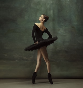 Mystic mood. graceful classic ballerina dancing, posing isolated on dark studio wall