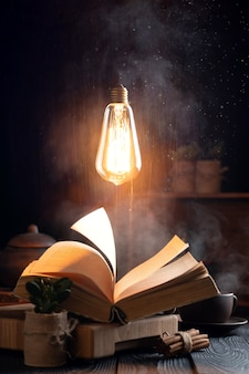 Mystic still life with a magic book, steam from a book and a burning light bulb hanging in the air. the text in the book is not readable