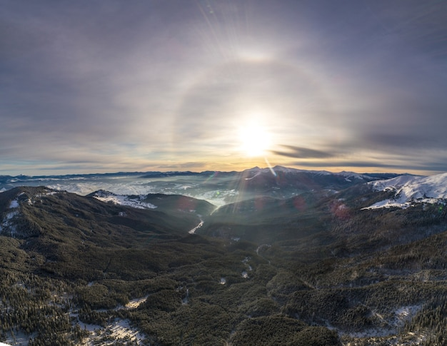 青い空と晴れた晴れた日に雪に覆われた山の丘と木々のスキー場の神秘的な空撮。環境にやさしい観光コンセプト。コピースペース