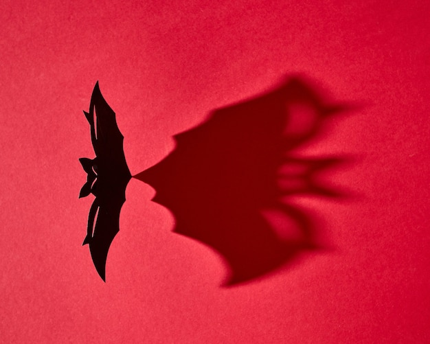 Mystical card made of hand craft paper bat with a pattern from a shadow on a red background with copy space for text. halloween. flat lay