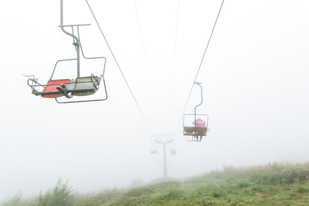 Мистический кресельный подъемник в тумане с людьми