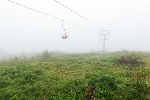Мистический пустой кресельный подъемник в тумане
