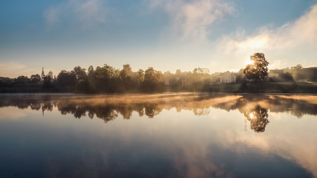Мистический утренний пейзаж с туманом над озером. мягкий фокус. панорамный вид.